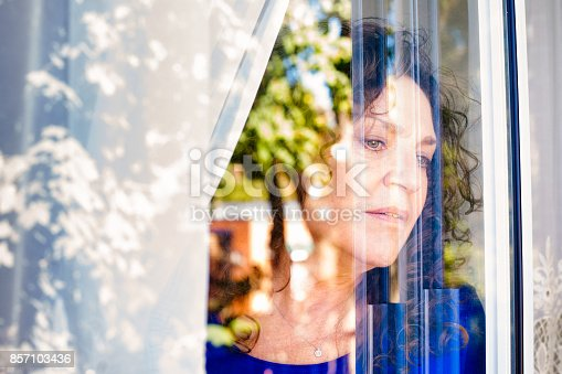 543048812 istock photo Mature Caucasian female looking cautiously out of a window 857103436