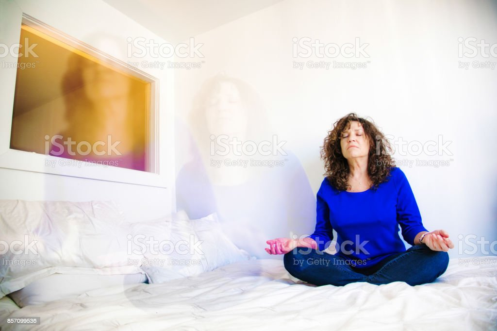 Mature Caucasian female practicing astral projection on her bed stock photo