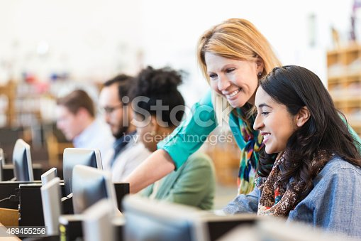 istock Mature Caucasian female professor assisting adult student in college library 469455256