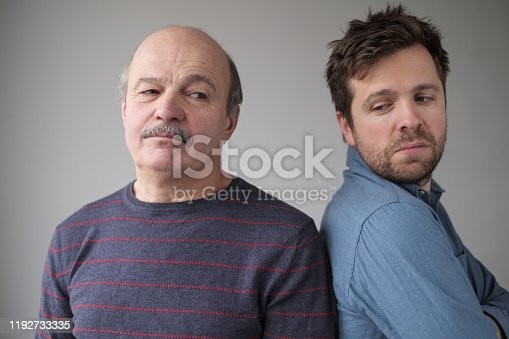 Mature caucasian man and son are offended on each other. Problems in family relationships.