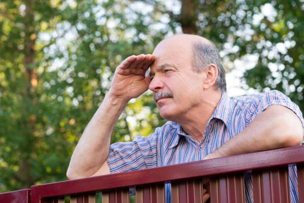mature caucasian man carefully watching over the fence. - vizinho imagens e fotografias de stock