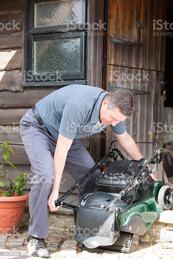 Mature Caucasian Man Moving a Lawn Mower stock photo