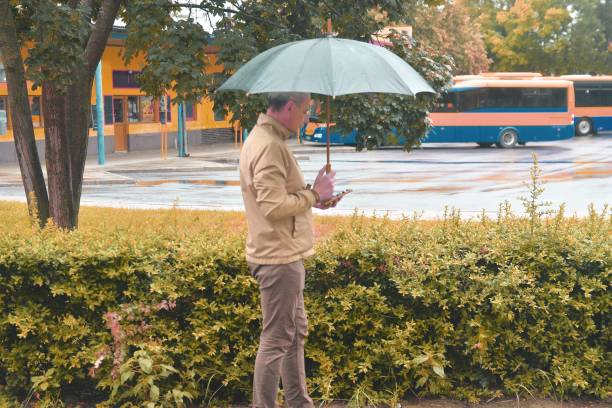 Mature caucasian man wearing a pastel jacket is using a smartphone under an umbrella. Man waiting on a bus, texting on mobile phone in a rainy day. Rainy day in a local town stock photo