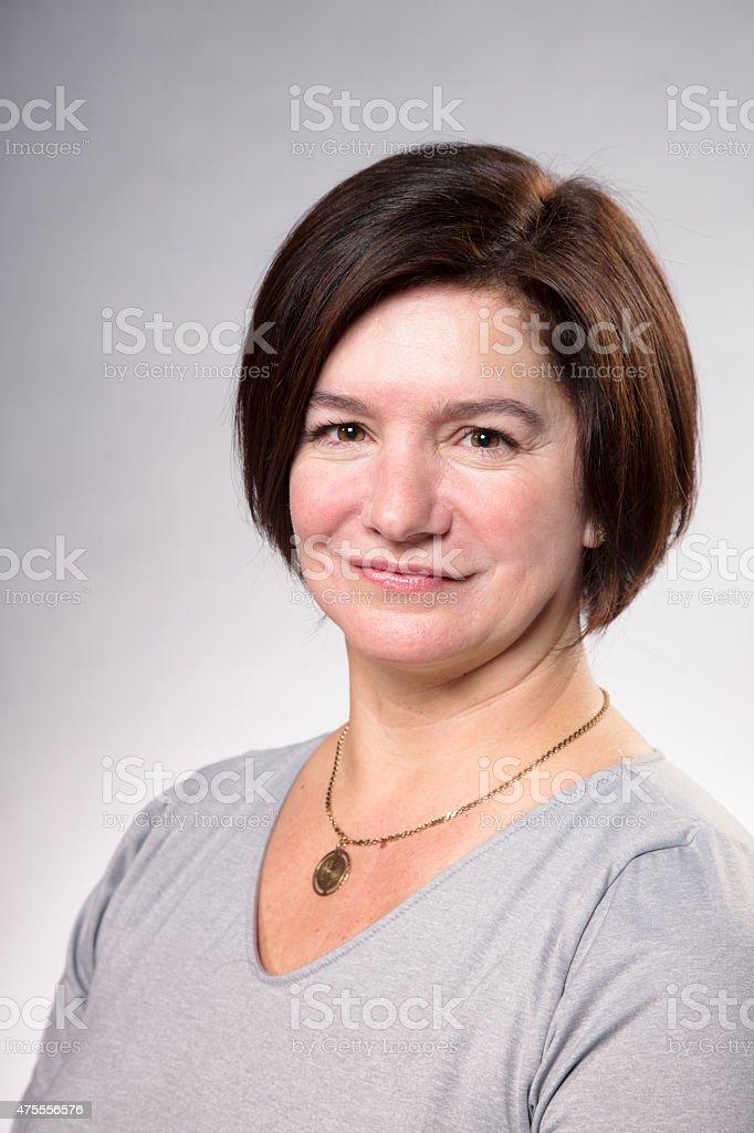 Mature Caucasian mother head and shoulders portrait smiling stock photo
