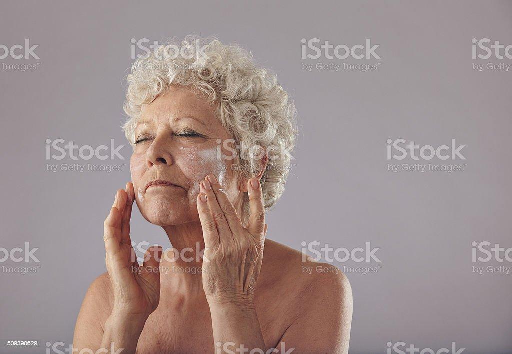 Matura donna caucasica applicando crema viso antirughe. foto stock  royalty-free 010b2ace8e0a