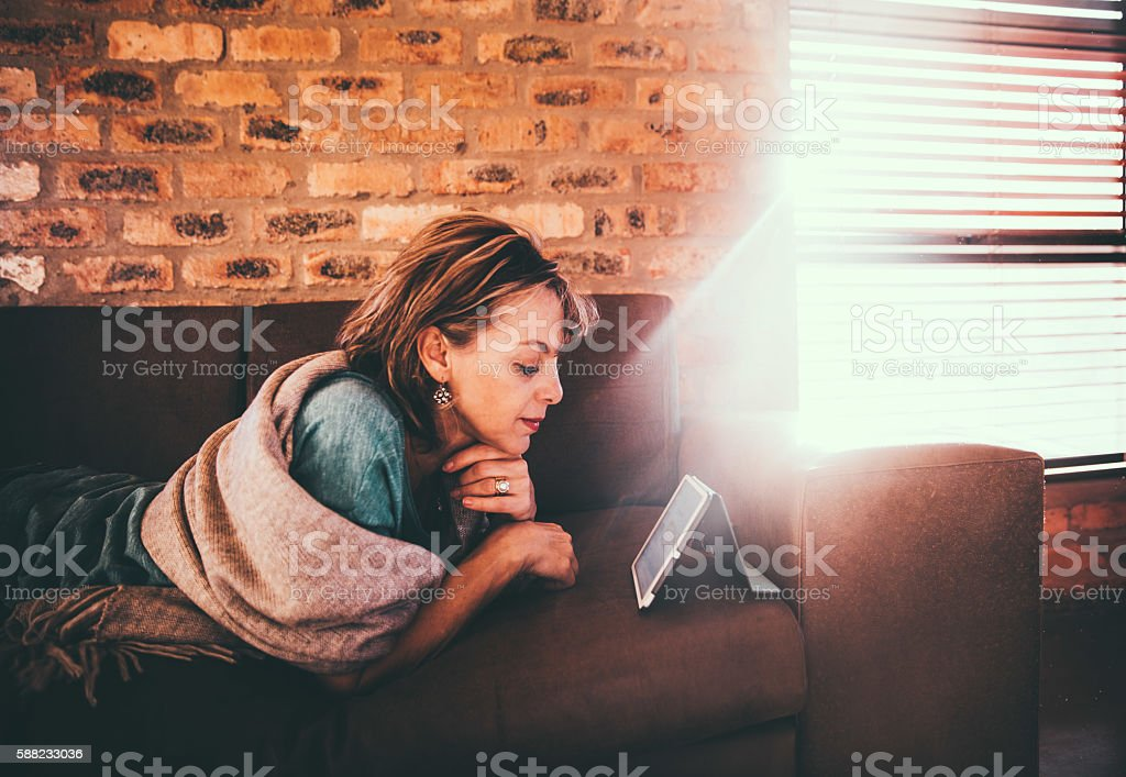 Mature caucasian woman reading newspaper on her digital tablet stock photo