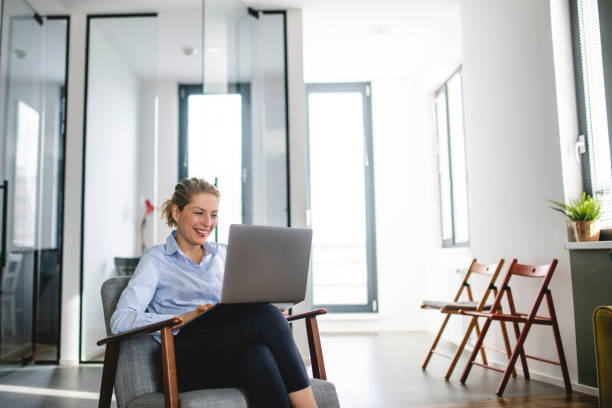 Mature Caucasian woman using laptop in the office stock photo