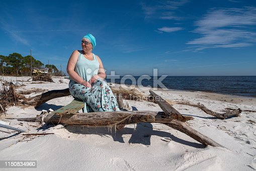 Mature Caucasian-White body-positive woman resting on the bench on a beach in North Florida, USA.