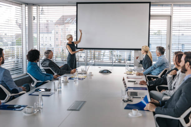 mature ceo giving a business presentation through projection screen in a board room. - projection equipment stock pictures, royalty-free photos & images