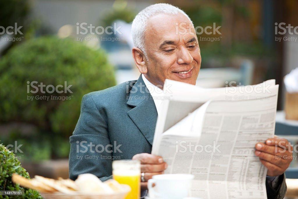 Mature cheerful businessman enjoying his morning juice and fresh newspaper. royalty-free stock photo