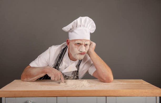 mature chef covered in flour looking annoyed and fed up - chef triste foto e immagini stock