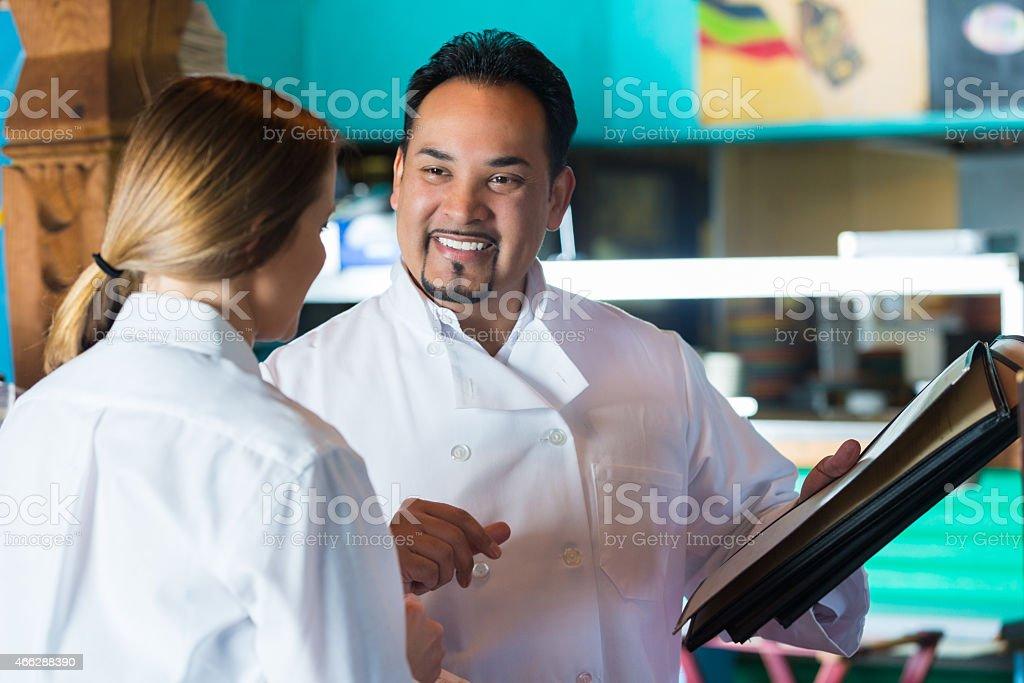 Mature chef in Tex-Mex restaurant training server with menu stock photo