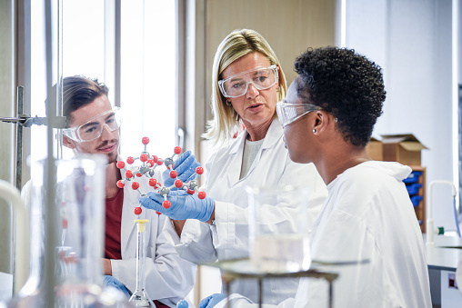 Two science students in laboratory wearing lab coats and safety goggles, learning about chemical structure