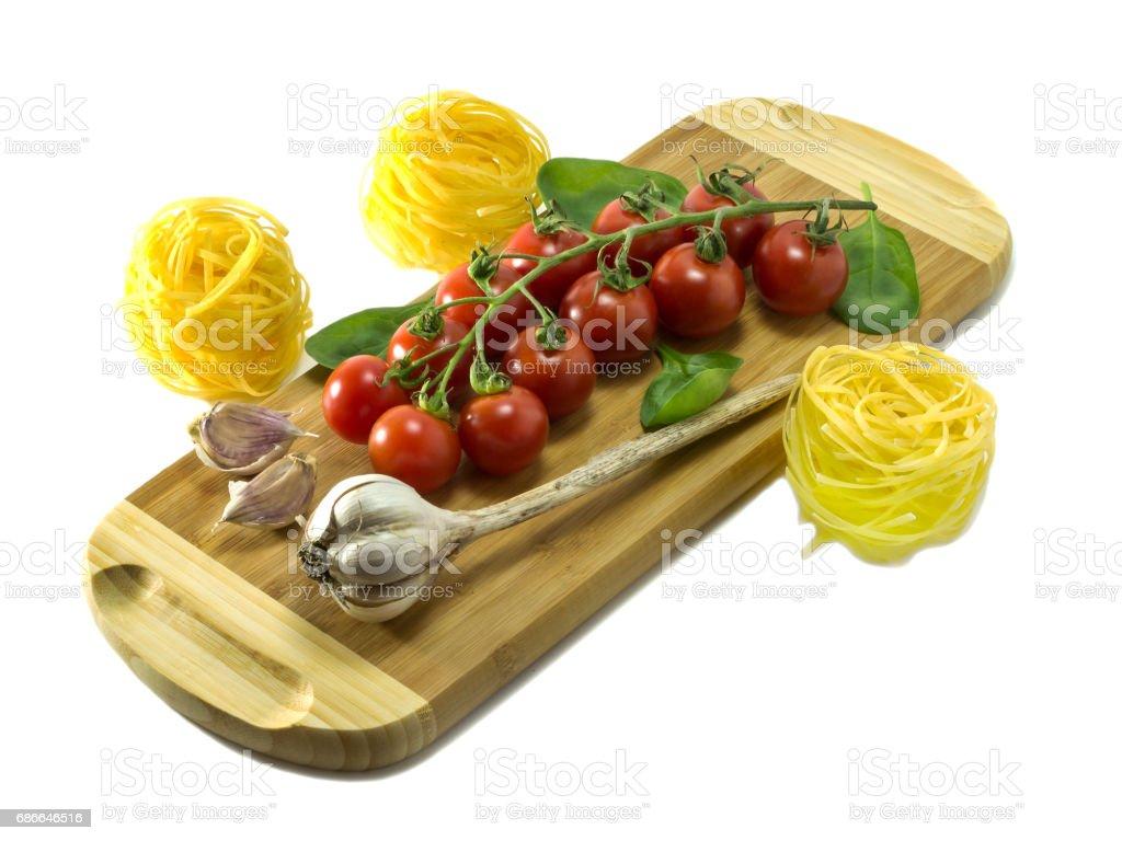 在白色背景上的砧板上的成熟櫻桃番茄。 免版稅 stock photo