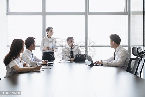 Mature Asian CEO sitting at the head of a meeting room conference table and speaking with junior executives.