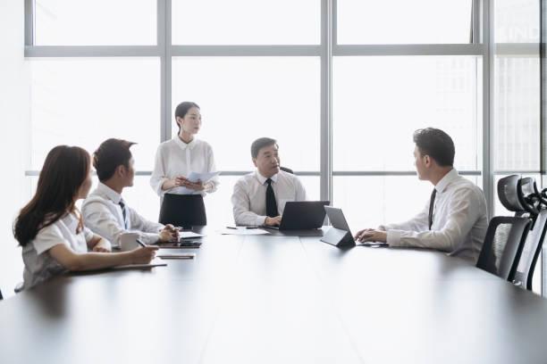 成熟した中国のceoが役員会で同僚と話す - ビジネスフォーマル ストックフォトと画像