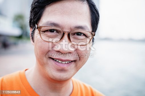 Cropped portrait of cheerful Chinese man in his 50s, wearing glasses,, happiness, individuality