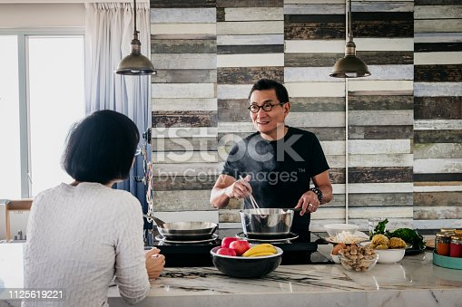 Man in his 50s cooking on hob and talking to woman sitting at counter, domestic life, food preparation, healthy lifestyle