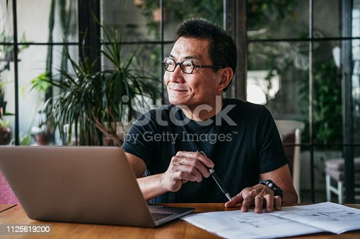 Cheerful man in his 50s sitting at table and looking away, doing paperwork, contemplation, ideas