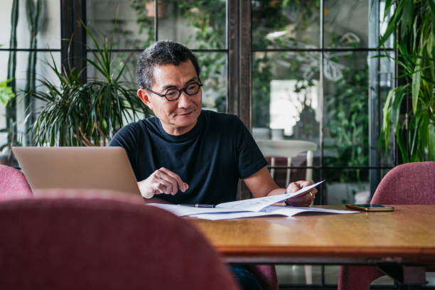 Mature Chinese man working from home on laptop stock photo