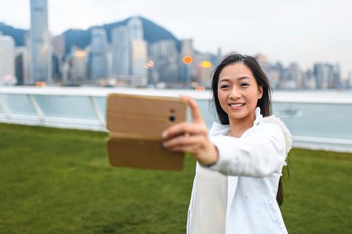 Mature Chinese Woman Taking Selfie at Ocean Terminal Deck