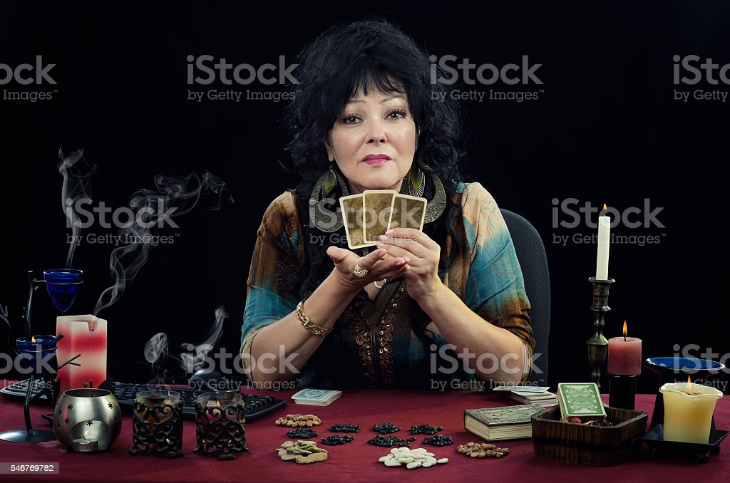 Mature clairvoyant holds three fortune telling cards stock photo