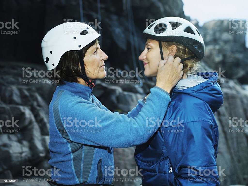 Mature climber helping younger with helmet, side view foto de stock royalty-free