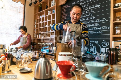 Chinese Mature coffee shop owner packing coffee in paper bags, woman is beside him