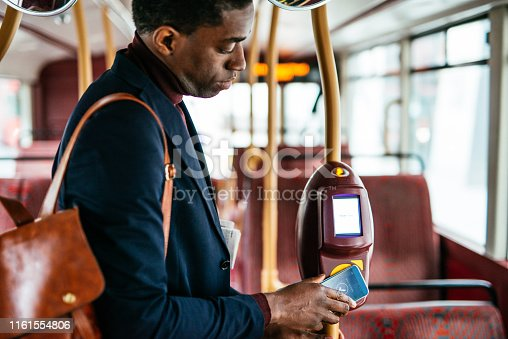Mature commuter in London using smart phone for contactless payment
