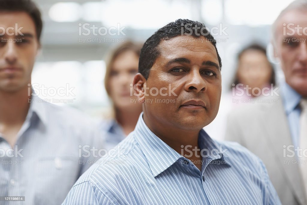 Mature confident business man with colleagues at the back royalty-free stock photo