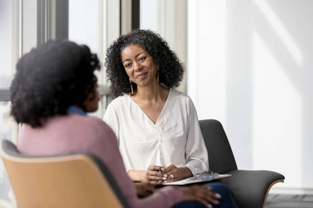 Mature counselor listens compassionately to unrecognizable female client The mature adult female therapist listens compassionately to the unrecognizable female client share her problems. counseling stock pictures, royalty-free photos & images