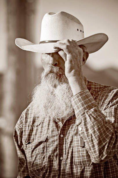 mature country cowboy avec barbe et moustache, son chapeau à dis bonjour de basculement. sépia tonifié. - chapeau de cow boy photos et images de collection