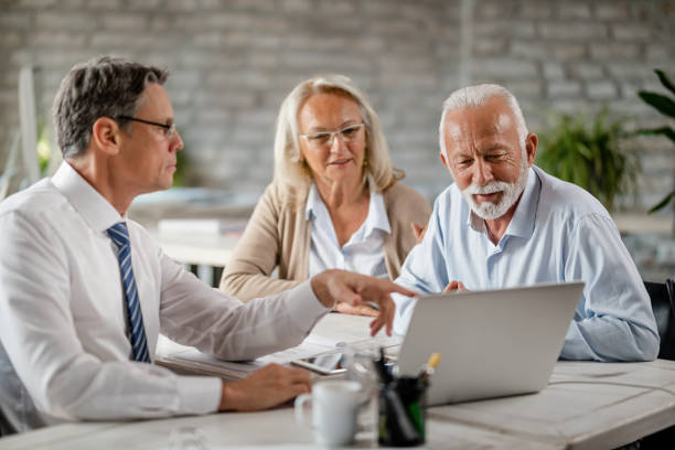 Mature couple and insurance agent using computer during consultations in the office. Senior couple using laptop with their financial advisor during a meeting int he office. Focus is on senior man. retirement stock pictures, royalty-free photos & images