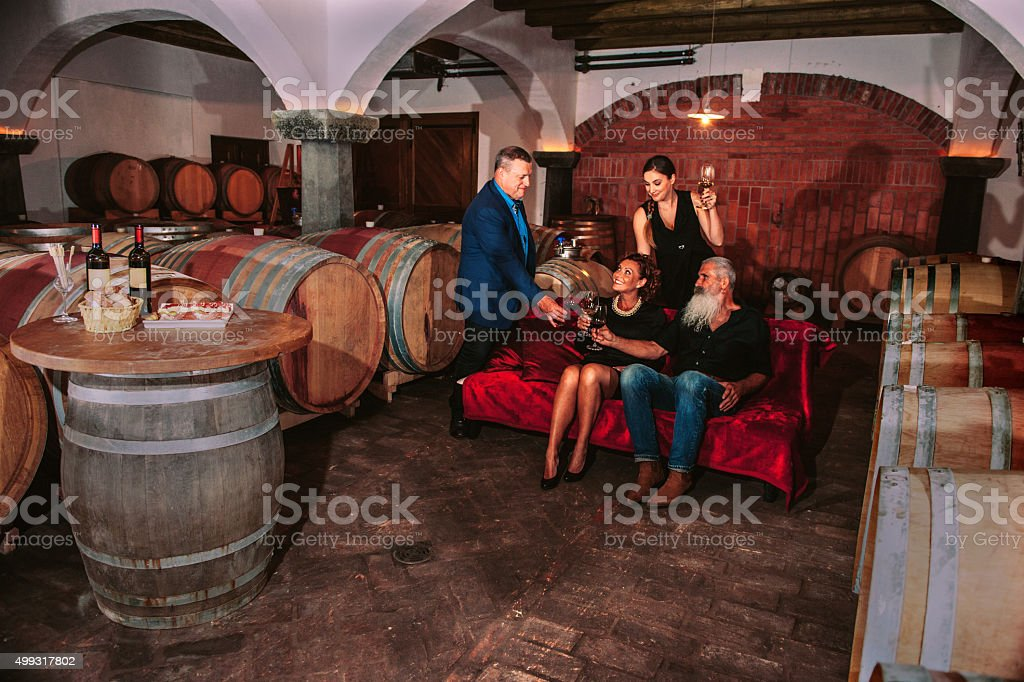 Mature Couple and Young Women Enjoying, Cellar in Europe stock photo