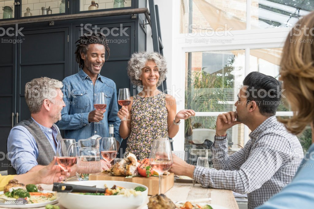 Mature couple at dinner table with wine glasses talking to friends stock photo