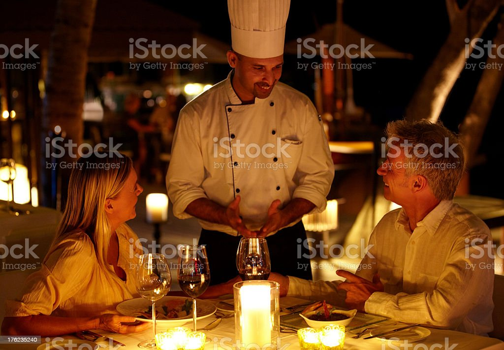 Mature couple at restaurant ordering food and drinks from the waiter stock photo