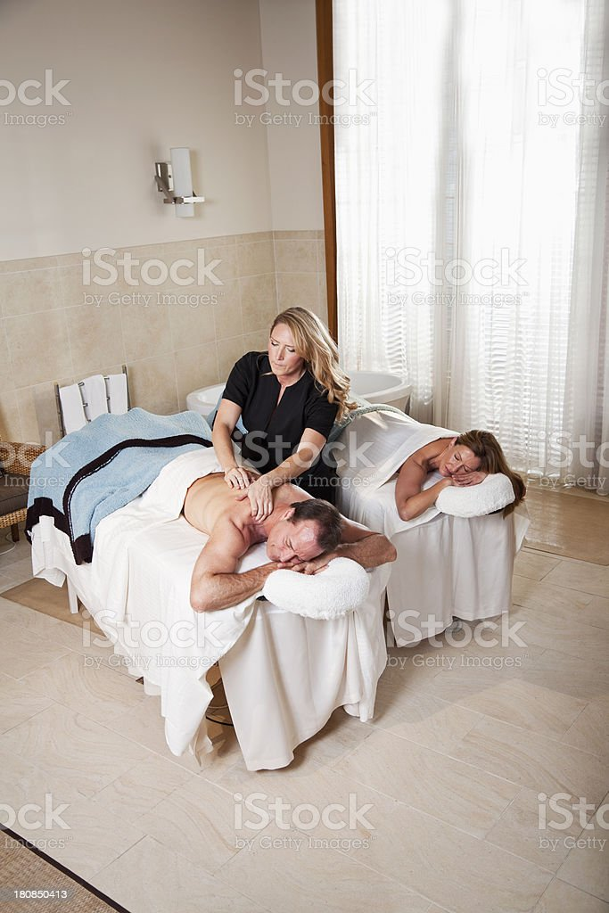 Mature couple at spa with massage therapist royalty-free stock photo