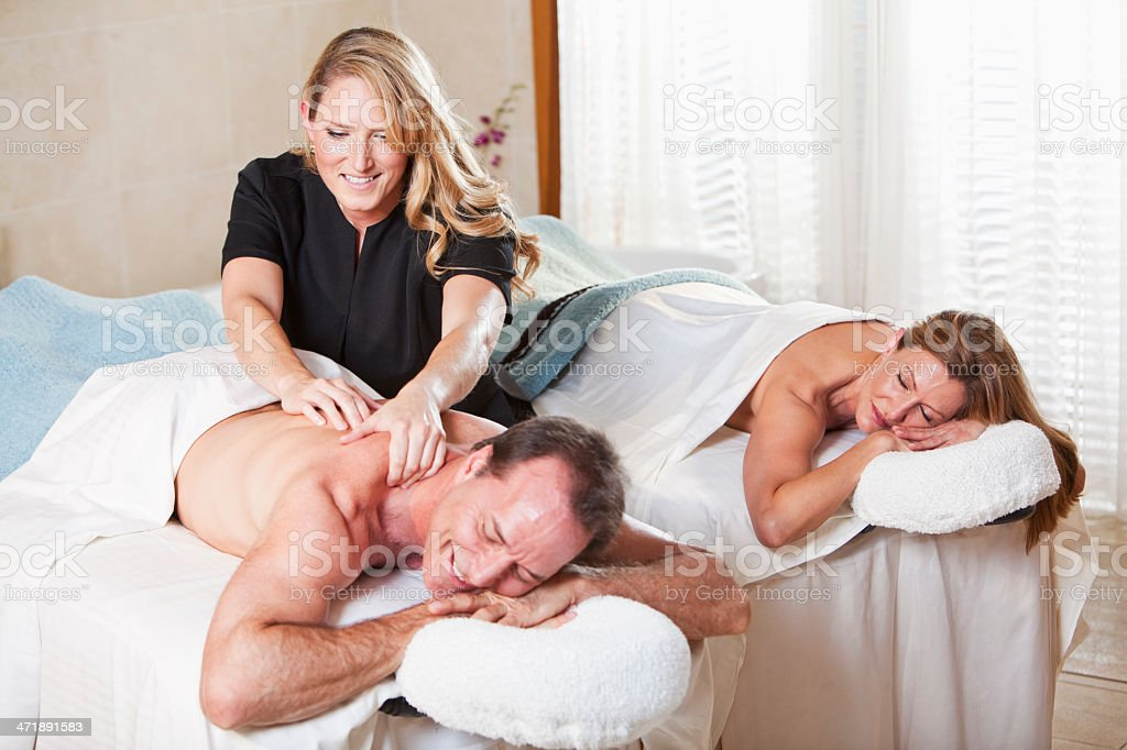 Mature couple at spa with massage therapist stock photo