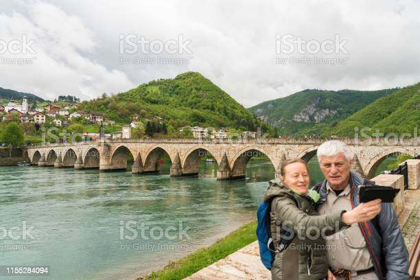 Mature couple at stone bridge in Višegrad