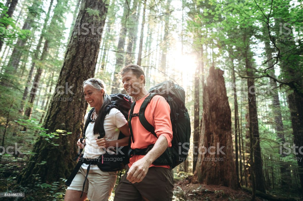 Mature Couple Backpacking in Forest stock photo
