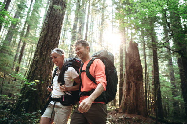 mature couple backpacking in forest - hiking stock photos and pictures
