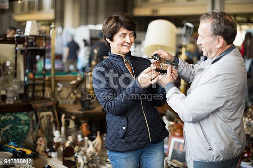 Mature family couple buying antique things at the fleamarket outdoor