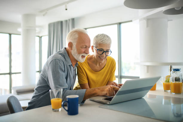 Mature couple buying some goods online Closeup top view of a mid 60's couple sitting at a kitchen counter and doing some online shopping. mature couple stock pictures, royalty-free photos & images