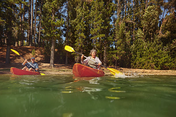 Mature couple canoeing on a lake during a camping trip stock photo