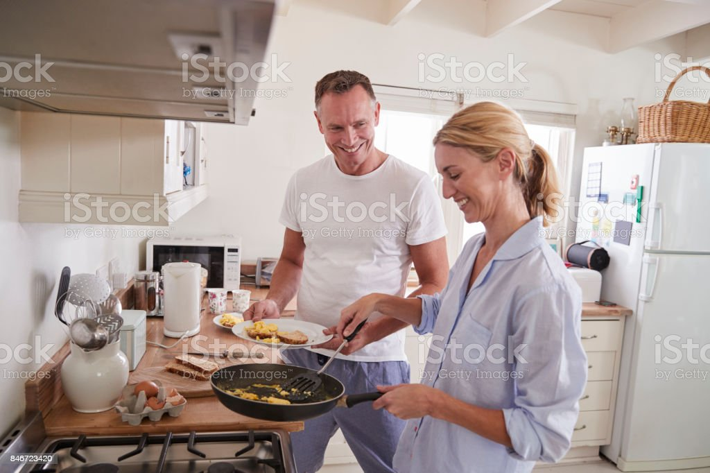 Mature Couple Chat In Kitchen As Woman Prepares Breakfast stock photo