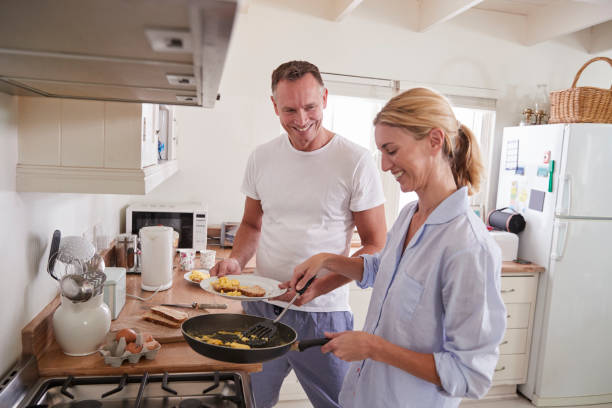 mature couple chat in kitchen as woman prepares breakfast - day in the life series stock pictures, royalty-free photos & images