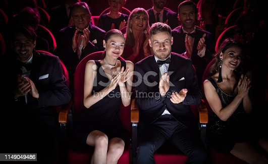 Mature couple clapping while watching theatrical performance. Happy man and woman are enjoying movie during weekend. They are sitting amidst crowd.