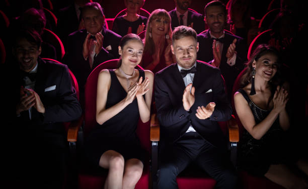 Mature couple clapping while watching opera Mature couple clapping while watching theatrical performance. Happy man and woman are enjoying movie during weekend. They are sitting amidst crowd. evening wear stock pictures, royalty-free photos & images