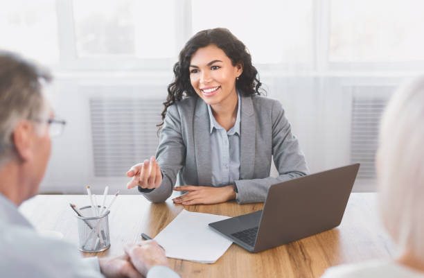 Mature couple consulting with financial adviser at office Expert. Senior couple sitting together at the desk and listening to their mexican financial advisor gesturing seller stock pictures, royalty-free photos & images