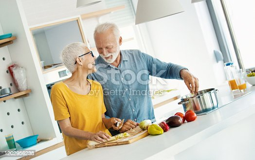 istock Mature couple cooking lunch together. 1202956238